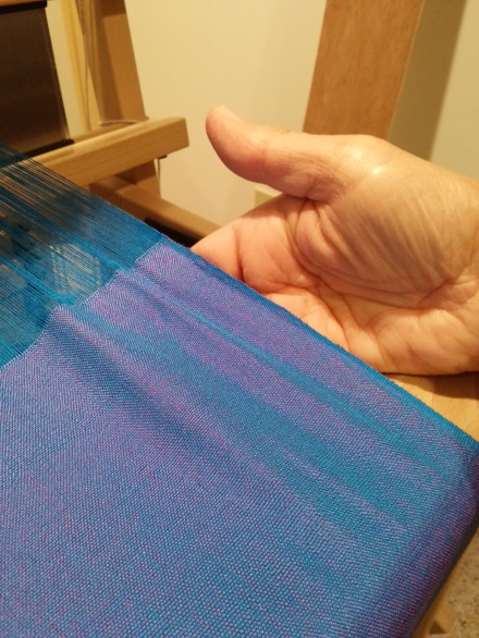When the finished cloth is wrinkled, alternating blue and violet highlights shimmer across it.